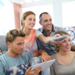 Photo: roommates watching tv with mobile devices