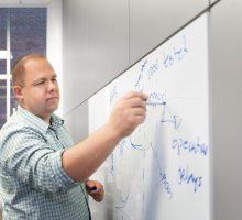 Professor David Larsen draws a graph on a white board in his office.